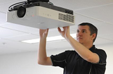 Photo of someone fixing a data projector