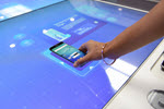 Hand putting phone on futuristic surface